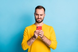 Photo of young unhappy upset sad unsure uncertain man see dislike bad comment in phone isolated on yellow color background