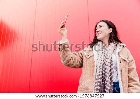 Photo of Young woman blogger stands in front of the red wall, holds a mobile phone in her hands and takes pictures, takes a selfie or communicates