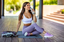 Photo of young Woman drinking water from bottle. Caucasian female drinking water after exercises or sport. Beautiful fitness athlete woman drinking water after work out exercising on sunset evening