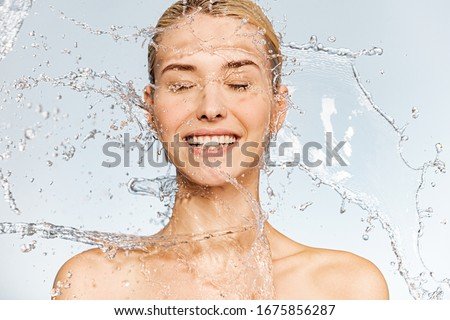 Photo of  young  woman with clean skin and splash of water. Portrait of smiling woman with drops of water around her face. Spa treatment. Happy girl washing her body with water. Water and body.