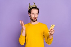 Photo portrait bearded man wearing golden crown reading fake news unhappy isolated pastel violet color background