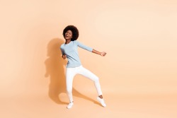 Photo portrait full body view of african american woman dancing enjoying party isolated on pastel beige colored background