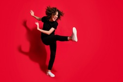 Photo portrait full body view of crazy rebel girl kicking raising leg isolated on vivid red colored background with blank space