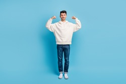 Photo portrait full body view of funny man flexing biceps wearing woolen hoodie isolated on pastel blue colored background