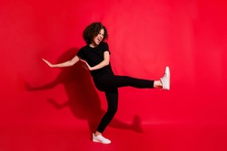Photo portrait full body view of girl kicking raising leg dancing isolated on vivid red colored background