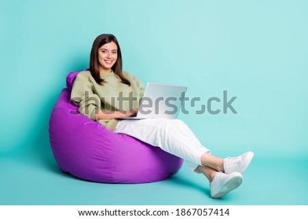 Photo portrait full body view of girl working on laptop sitting in purple beanbag armchair isolated on vivid teal colored background