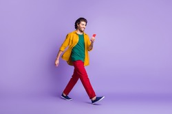 Photo portrait full body view of guy walking holding phone in one hand isolated on vivid purple colored background