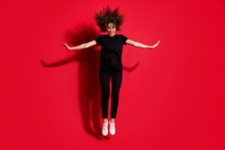 Photo portrait full body view of happy girl jumping up with hands to both sides isolated on vivid red colored background