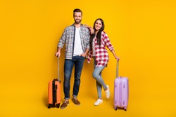 Photo portrait full body view of man and woman getting ready for trip with suitcases isolated on vivid yellow colored background