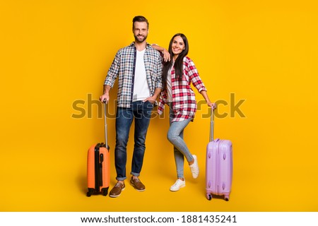 Photo portrait full body view of man and woman getting ready for trip with suitcases isolated on vivid yellow colored background Foto stock ©