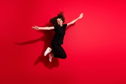 Photo portrait full body view of woman spreading hands like plane jumping up isolated on vivid red colored background