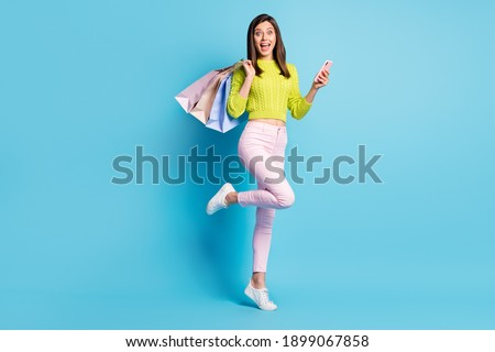 Photo portrait full body view of woman standing on one leg holding phone shopping bags isolated on pastel blue colored background