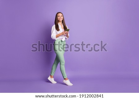 Photo portrait full body view of woman walking holding phone in two hands isolated on vivid purple colored background Foto stock ©