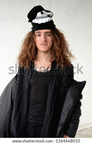 photo portrait funny guy with long curly hair in black clothes on a white background