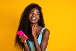 Photo portrait of african american woman with long wavy hair holding pink smartphone in two hands laughing wearing blue singlet isolated on vivid, yellow colored background