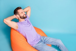 Photo portrait of bearded hipster chilling during break laying on beanbag smiling isolated on bright blue color background copyspace