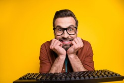 Photo portrait of bearded man staring mad crazy nerd programmer with keyboard eyewear isolated on vivid yellow color background