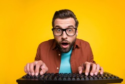 Photo portrait of bearded man staring playing video game crazy nerd pressing keyboard spectacles isolated on bright yellow color background