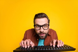 Photo portrait of bearded student playing video game crazy geek with keyboard in glasses isolated on vibrant yellow color background