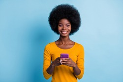 Photo portrait of beautiful cheerful black skinned girl using social media isolated on vivid blue color background