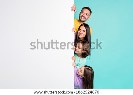 Photo portrait of big family hiding behind big white placard poster with small children isolated on vivid teal colored background