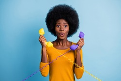 Photo portrait of black skinned amazed curly woman holding two retro phone handsets with wires isolated on vivid blue color background