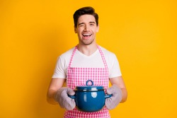 Photo portrait of blinking guy holding blue pot wearing kitchen gloves isolated on vivid yellow colored background