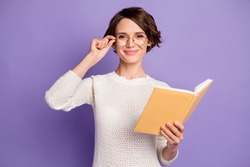 Photo portrait of clever female student touching spectacles keeping book isolated on bright violet color background
