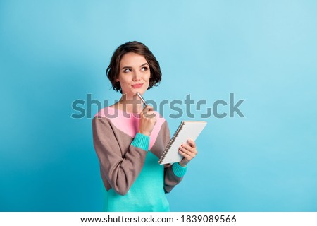 Photo portrait of curious girl thinking about idea keeping pen notebook looking at copyspace isolated on bright color blue background