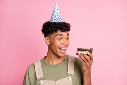 Photo portrait of curly boy eating birthday cake smiling wearing festive cone overall isolated on pastel pink color background