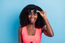 Photo portrait of curly woman funky winking blinking overjoyed isolated vibrant blue color background