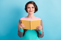 Photo portrait of cute female girl with short hair keeping yellow book smiling isolated on bright blue color background