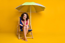 Photo portrait of dreamy girl sitting in blue deckchair under beach umbrella holding head glasses with hand wearing pink swim wear isolated on bright yellow colored background