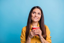Photo portrait of dreamy woman looking empty space biting lip keeping mug with beverage isolated on bright blue color background