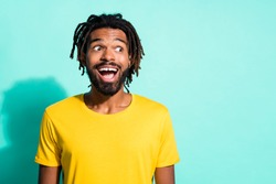 Photo portrait of ecstatic black skin man looking at blank space isolated on vivid cyan colored background