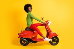 Photo portrait of excited african american woman driving a red scooter with legs spread wearing casual outfit isolated on vivid yellow colored background