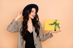 Photo portrait of excited girl holding small yellow present box isolated on pastel beige colored background
