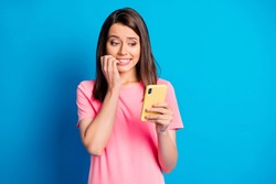 Photo portrait of female blogger biting fingers nervous using mobile phone isolated on vibrant blue color background