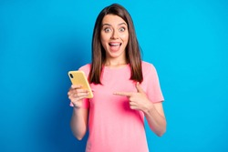 Photo portrait of female blogger pointing finger at mobile phone staring isolated on bright blue color background