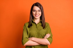 Photo portrait of female freelancer smiling with folded hands wearing glasses green shirt isolated on bright orange color background