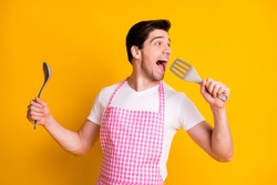 Photo portrait of funny man singing into spatula isolated on vivid yellow colored background