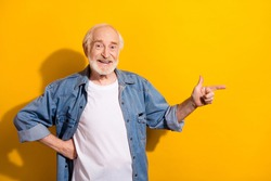Photo portrait of grandfather pointing finger blank space recommending isolated vibrant yellow color background