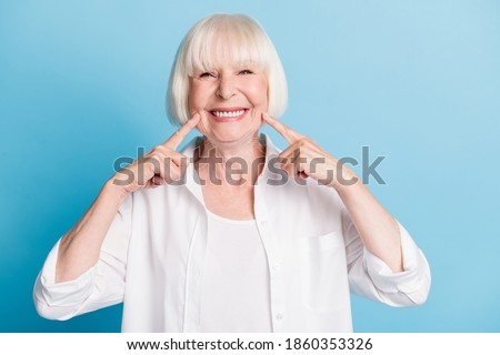 Photo portrait of granny blonde hair pointing at white teeth healthy smile dental whitening veneers isolated on bright blue color background