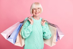 Photo portrait of granny carrying bags after black friday sale wearing glasses isolated on pastel pink color background