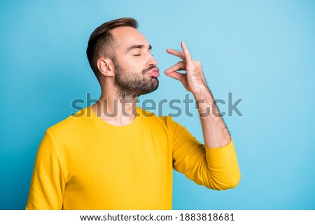 Photo portrait of guy with pouted lips showing gourmet sign with fingers tasty delicious isolated on vibrant blue color background
