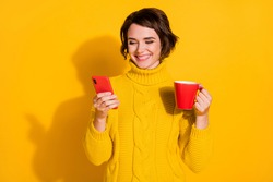 Photo portrait of happy cute female student using smartphone holding cup of tea isolated on bright yellow color background