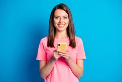 Photo portrait of happy female student keeping mobile phone smiling isolated on bright blue color background