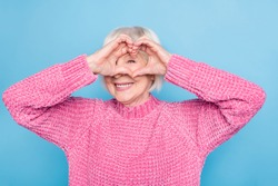 Photo portrait of old lady making heart shape with fingers on one eye looking through it isolated on pastel blue colored background