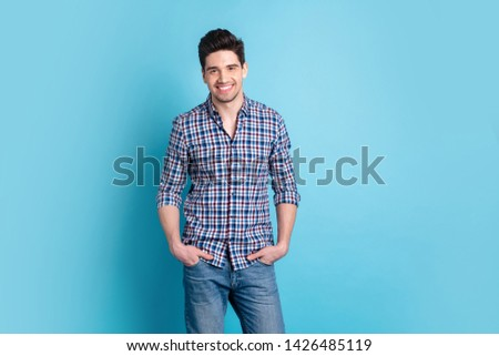 Photo portrait of optimistic nice glad cute with haircut hairdo standing guy holding palms in pocket of denim trousers isolated pastel background copy space