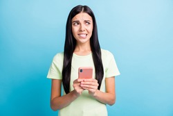 Photo portrait of panicking girl biting lower lip holding phone in two hands isolated on pastel blue colored background
